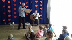 Dzieci siedzą na podłodze, są zwrócone w kierunku dwóch panów. Jeden z nich trzyma w rękach gitarę, a drugi bębenek.