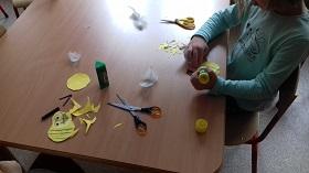 Dziecko siedzi przy stoliku, w ręku trzyma klej. Na stole znajdują się artykuły plastyczne takie jak: klej, nożyczki, żółte kółka papierowe, piórka.