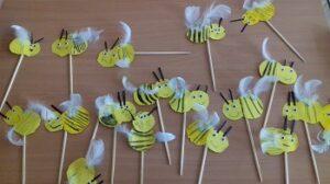 Na stoliku znajdują się pszczoły. Każda wykonana z dwóch żółtych kółek, piórek, oczek, kredek. Przyczepione są do drewnianych patyczków.