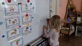 Dziewczynka stoi przy tablicy magnetycznej i rysuje rzeczy w kształcie trójkąta niebieskim pisakiem