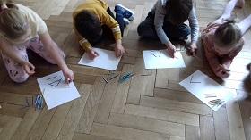 Czwórka dzieci siedzi na podłodze w sali. Na białych kartkach A4 układa z kolorowych patyczków trójkąty.