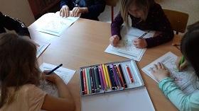 Dzieci siedzą przy stole. Kredkami kolorują karty pracy. Na stole leży pudełko kredek