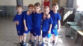 Piątka chłopców pozuje do zdjęcia w niebieskich strojach sportowych
