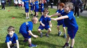 Piątka chłopców rozgrzewa się przed meczem wykonując przysiady