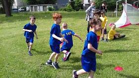 Piątka chłopców rozgrzewa się przed meczem wykonując slalom pomiędzy przeszkodami
