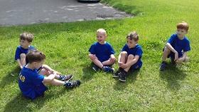Piątka chłopców siedzi na trawie