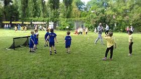 Piątka chłopców stoi po bramką z piłką. Po prawej stronie stoi dwóch przeciwników. W tle widać sędziego