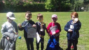 Piątka chłopców stoi na trawie. W rękach trzymają dyplomy, medale oraz puchar