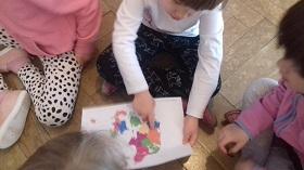 Dziewczynka wskazuje palcem innym dzieciom mapę Danii