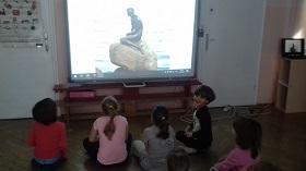 Dzieci siedzą przed tablicą interaktywną. Na tablicy widać zdjęcie małej syrenki