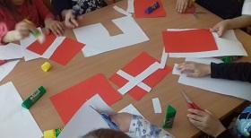 Na stoliku znajdują się czerwone i białe kartki, kleje i nożyczki. Dzieci wycinają białe paski i przyklejają je na czerwoną kartkę