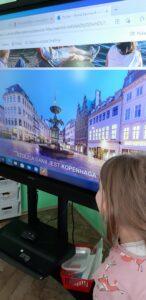 Przed tablicą stoi dziewczynka, na ekranie wyświetlony jest slajd przedstawiający fontannę w Kopenhadze.