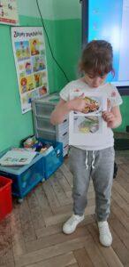Dziewczynka wskazuje na zdjęciu potrawę rybną.