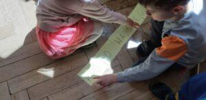 Dwoje dzieci układa napis –KRÓLOWA ŚNIEGU.