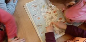 Na stoliku leży książka przedstawiająca mapę Danii, dziecko wskazuje miejsce Legolandu.