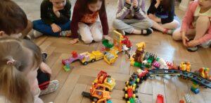 Dzieci siedzą w półkolu, patrzą na ułożone budowle z klocków Duplo.
