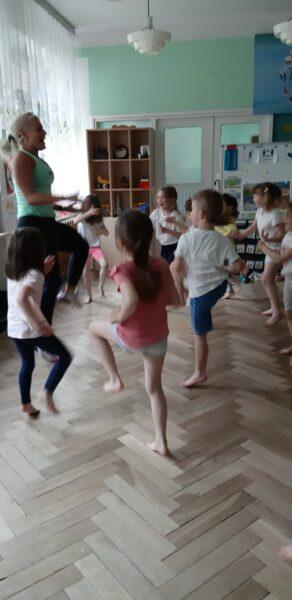 Dzieci w strojach gimnastycznych patrzą na panią i podnoszą nogę do góry.