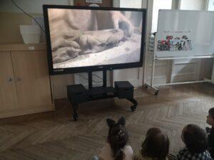 Dzieci siedzą przed monitorem