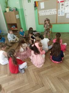 dziewczynka siedzi i czyta dzieciom bajkę