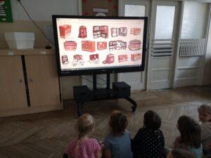 dzieci oglądają prezentację o apteczkach na monitorze