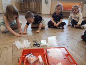 dzieci na podłodze oglądają zawartość apteczki