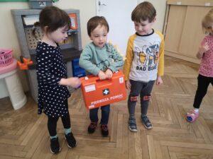 troje dzieci trzyma w ręku podróżną apteczkę