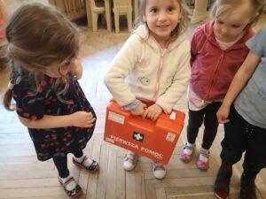 dzieci stoją, jedno z nich trzyma w ręku podróżną apteczkę