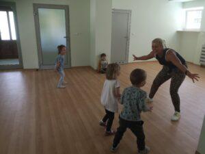 dzieci bawią się na sali gimnastycznej, pani instruktorka stoi przed nimi