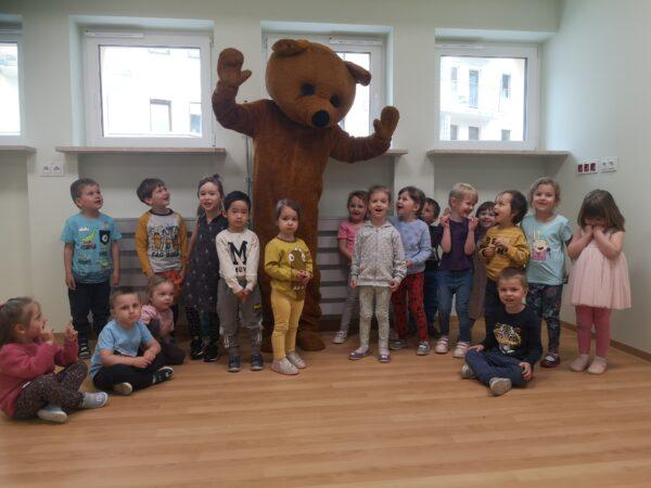 dzieci pozują z misiem do zdjęcia