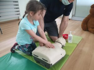 dziewczynka wykonuje resuscytację na fantomie