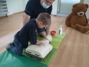 chłopiec wykonuje resuscytację na fantomie