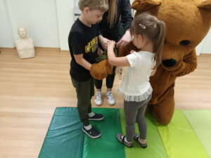 dwoje dzieci zakłada misiowi opatrunek