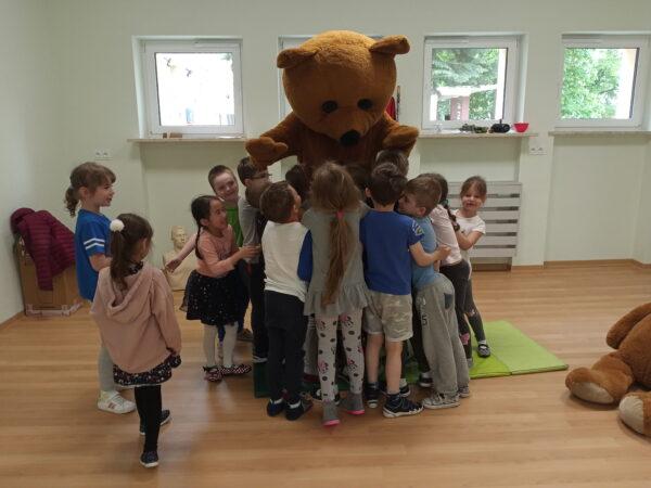 dzieci przytulają misia Edzia