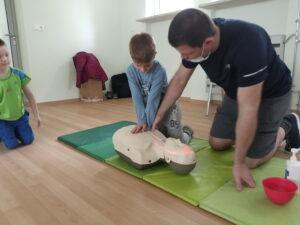 mężczyzna pokazuje dziecku jak wykonać masaż serca