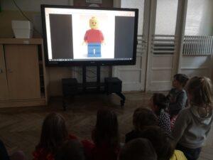 dzieci na monitorze oglądają ludzika lego