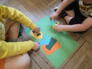dwoje dzieci nakleja na karton sylwetę ludzika lego