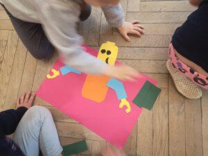 dziecko układa z pociętych kawałków sylwetę lego