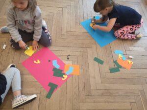 dzieci na podłodze układają sylwetę ludzika lego