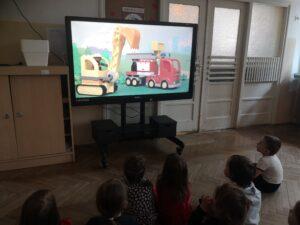 dzieci na monitorze oglądają bajkę Lego