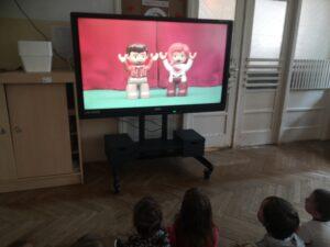 dzieci oglądają na monitorze ludziki lego