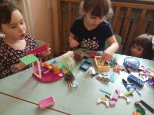dzieci przy stole bawią klockami lego na stole