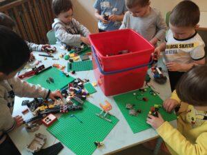 dzieci na stole bawią się klockami lego