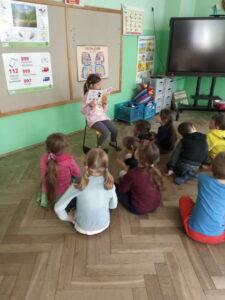 dziewczynka siedzi na krzesełku i trzyma w ręku książkę. Na przeciwko niej siedzą dzieci i słuchają