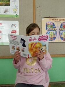 dziewczynka trzyma w rękach książkę i czyta dzieciom na tle tablicy