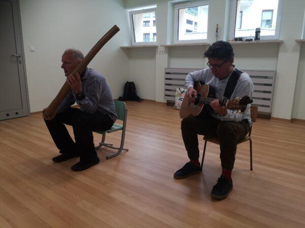 dwóch mężczyzn siedzi na krzesłach, w ręku trzyma instrumenty muzyczne.