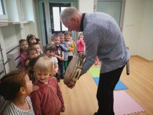 mężczyzna prezentuje dzieciom bębenek