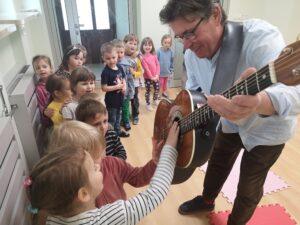 dzieci dotykają gitary