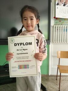dziewczynka trzyma dyplom