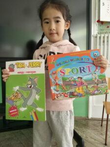 dziewczynka trzyma nagrody konkursowe