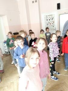 dzieci stoja w sali i patrzą się w kamerę
